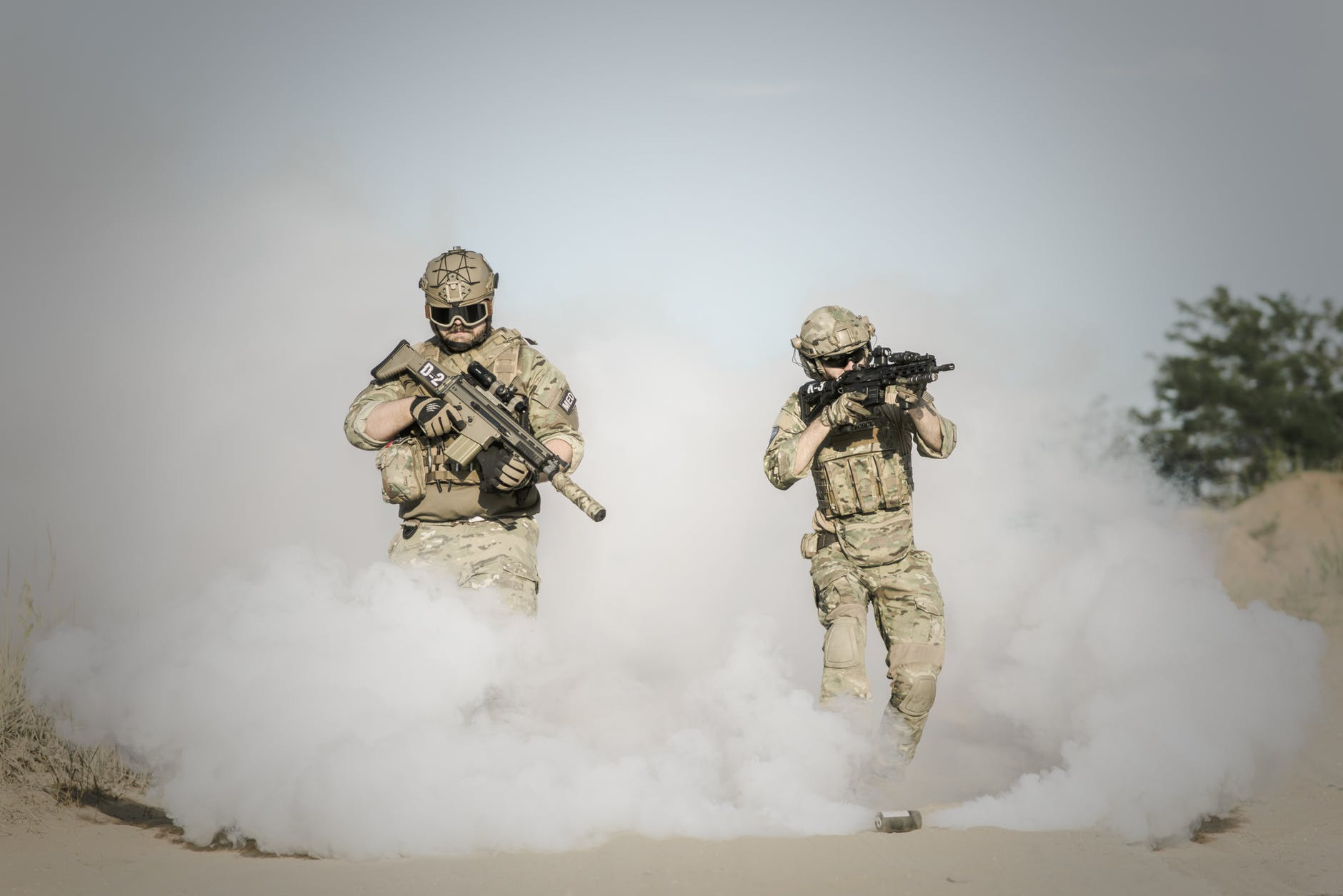 men holding rifle while walking through smoke grenade