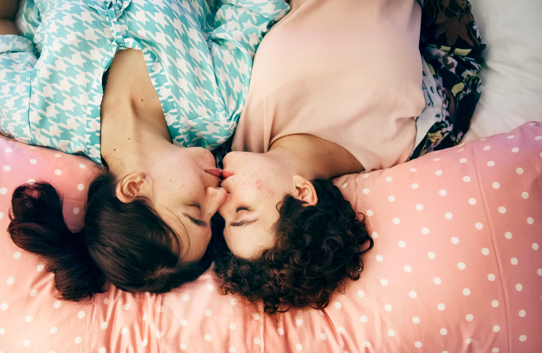 two woman kissing on bed